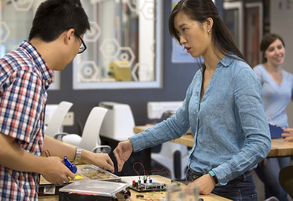 Image showing two students collaborate on an electronics project at the BeAM@Murray Hall makerspace.